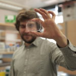 Phil Romero holds a microfluidic device he uses in his research.